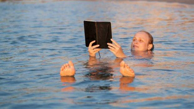 Woman Smiling She Reads Book While Swimming Floating